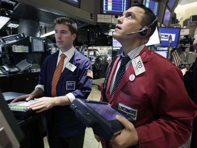 Stocks slide, and investors wait for earnings