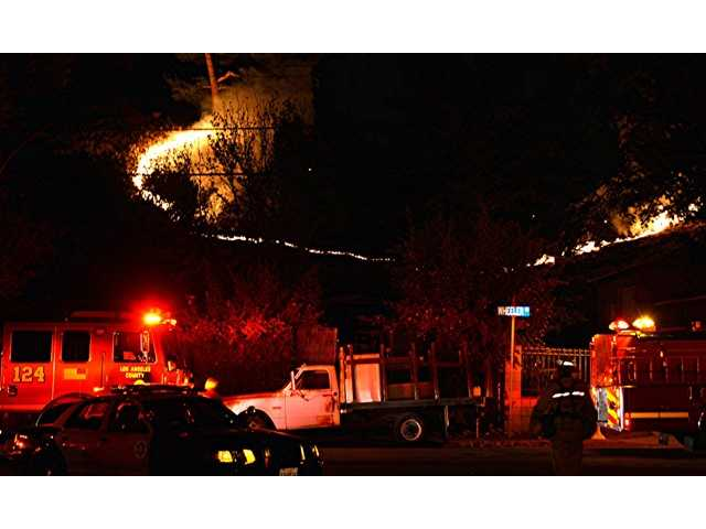 Brush fire erupts behind Newhall home