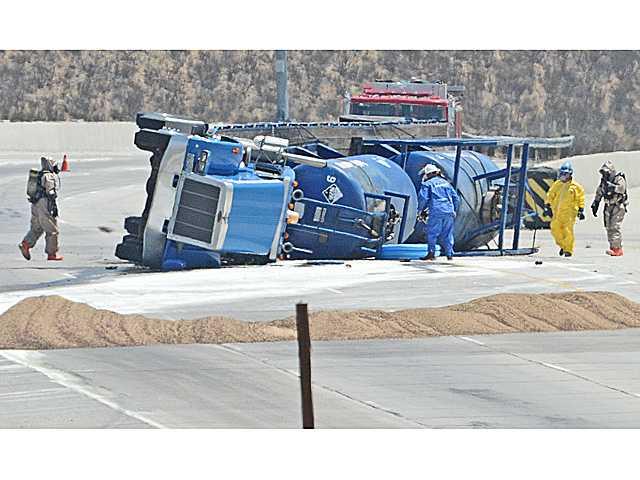 UPDATE: Tanker truck overturns, spills corrosive chemical