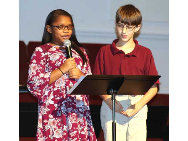 "Andrea Hunter and Micah Rose take turns reading excerpts from the Mary Angelou's ""I Am Human"" during Thursday's event at First Baptist Church of Rincon."