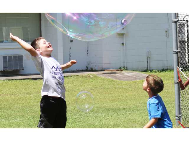 Brothers Noah and Jacob Tyndall, ages 4 and 7, respectively, try to pop a gigantic bubble created by their father, Jonathan Tyndall, during the Aug. 11 Scout Pack 691 Back-to-Scouting Picnic at Zion Lutheran Church.