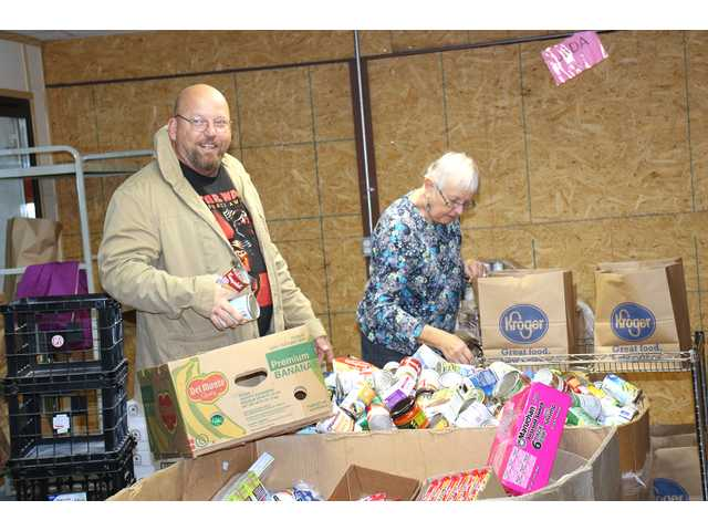 Bobby Tilley and Mary Hughes prepare bags for clients at the Manna House Ministries pantry on Nov. 14.