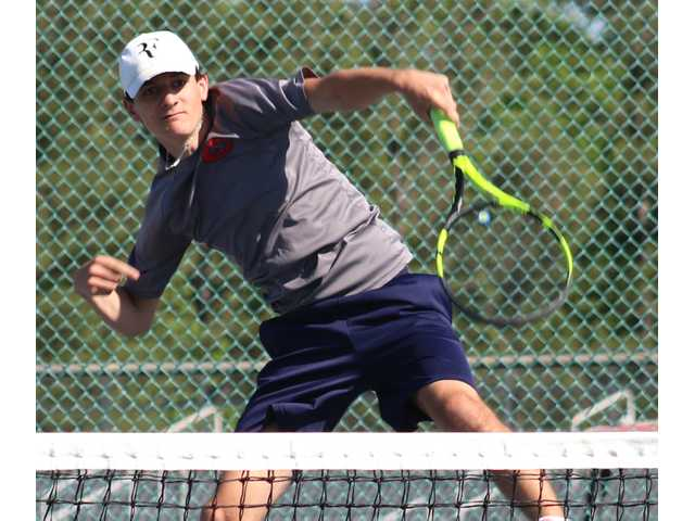 Clark Heller goes high to put away a shot in the second set of his singles match Wednesday.