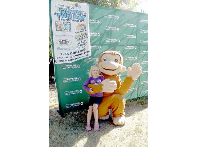 Sophia Nelson poses for a photo with Curious George, Saturday at the Great Bend Brit Spaugh Zoo. Smoky Hills Public Television sponsored Family Fun Day, a free event that will repeat today from 10 a.m. to 2 p.m. at the zoo.