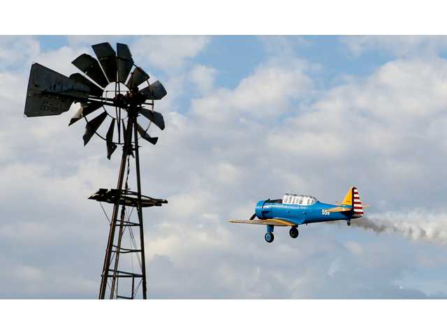 A 1930s airplane flies over the 17th Annual Santa Fe Trail Tired Iron Show on Saturday.