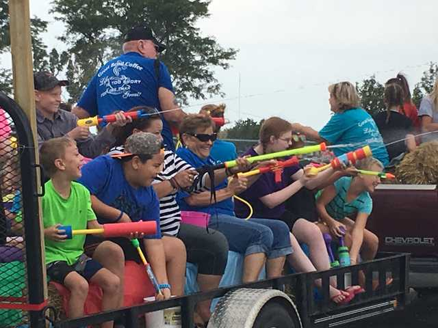 Riders on the Great Bend Coffee float could hardly wait to let loose on the crowd of spectators who were equally prepared with squirt sticks during the first ever Party in the Park Wet-Dry Parade Saturday morning.