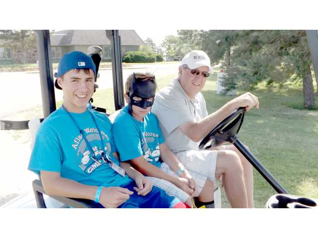 Campers John Kaberline, Topeka, left, and Alec Barber, Pleasant Valley, Mo., are accompanied to the fourth hole of the Stoneridge Country Club by Topeka's Jim Lee, one of the sponsors of the annual golf outing.