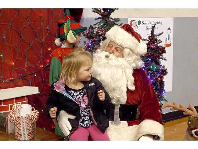 Hundreds of children visit Santa's Workshop, Monday at the Great Bend Municipal Auditorium. Above: Lynnex Swanson, 2, sits on Santa's lap.