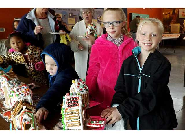 Children collect the gingerbread birdhouses they made Saturday at the Kansas Wetlands Education Center's open house. Sisters Camdyn Post, 8, right, and Halle Post, 10, of Great Bend show their creations.