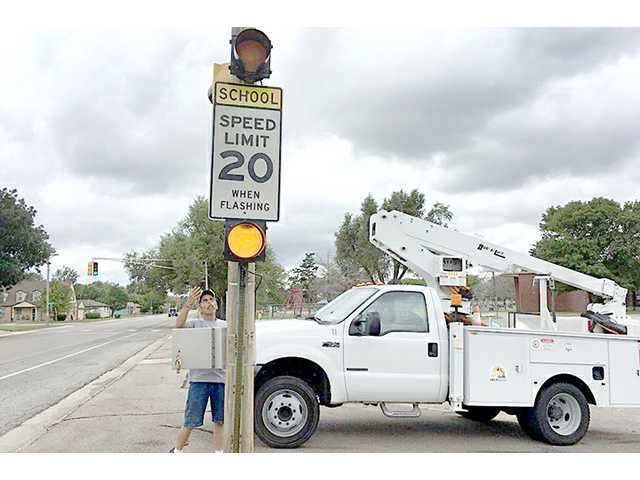 A City of Great Bend Street Department employee prepares a school crossing light to come on at Holy Family School for the upcoming school year.