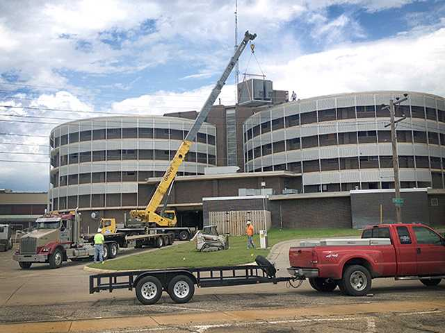 The Verizon control box is removed from the top of the former St. Rose Health Center in preparation for demolition of the circular towers starting Monday. The new St. Rose opened recently next door.