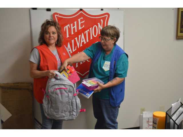 Salvation Army Store Manager Dana Walls and her employee Mary Snell pack a backpack for a back to school drive for Barton County on Wednesday.