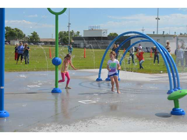 Kids play in the new splash pad in Ellinwood on Thursday after the ribbon cutting ceremony.