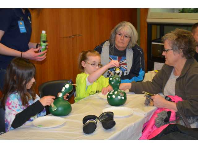 """Children decorate a birdhouse made out of a gourd at the Kansas Wetlands Education Center on Saturday. KWEC held a winter kids program called """"Celebrate Birds."""" The children got a chance take a walk along the nature trails to identify birds."""