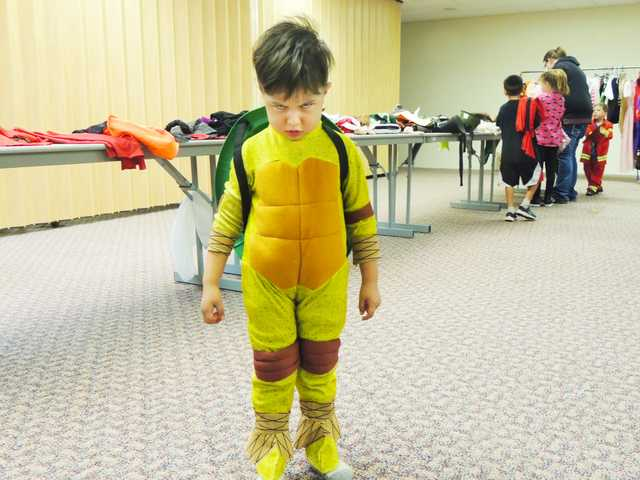 A child gives a fierce Ninja Turtle scowl after trying on a costume Saturday at the Great Bend Public Library.