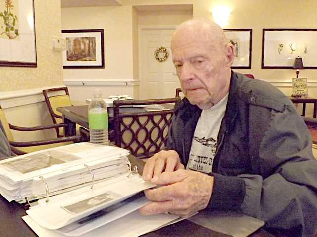 Mildon Yeager is shown with his collection of photos showing the restoration of Fort Larned.