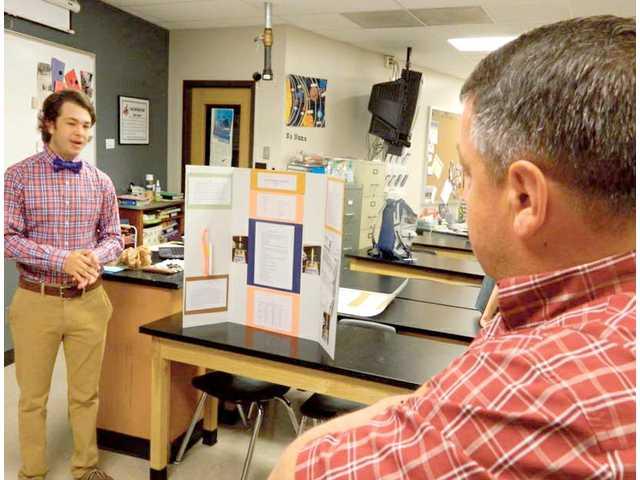 Above: Ken Botzung, Great Bend High School science teacher, asks Wyatt Rugan about his rocketry project. Wyatt is the son of Cheryl Rugan, school board member. Below: Dorian Lueth strums a guitar he built to help explain the effects of sound and resonance.