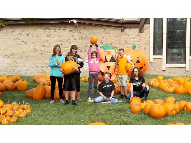 Members of the middle school youth group at First Christian Church show off some of the pumpkins for sale at the Pumpkin Patch, an annual fundraiser for their mission trips. Sales also help farmers from the Navajo Nation who grow the pumpkins in New Mexico.
