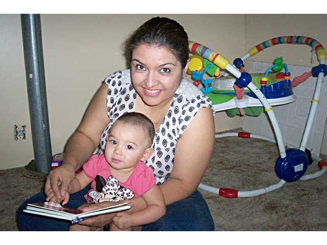 Victoria Sanchez, new Sunflower Diversified Services translator, interacts with little Evelyn.