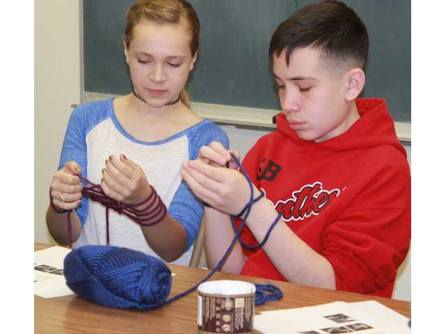 Alexa Straub shows another youth how to get started with arm knitting at the Fiber Arts Fun Day held Thursday.