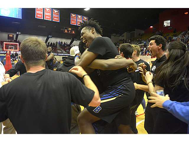 """Barton's hero """"Squeaky"""" Wilkins bear hugs a teammate following the Cougars' 85-83 victory over No. 1 ranked Indian Hills, Iowa."""