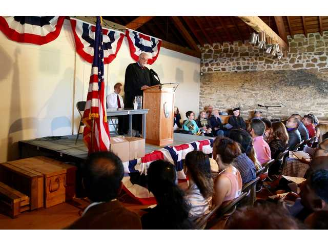 District Court Judge J. Thomas Martin welcoming new citizens