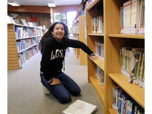 A volunteer shelves books in June at the Manteca Library.