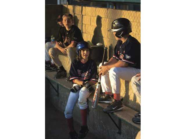 Members of a William S. Hart All-Star team sit in the dugout on July 22 in a game against Kampgrounds of America Kangaroos of Australia at the Hart Complex. Children today play sports like baseball and soccer year-round.