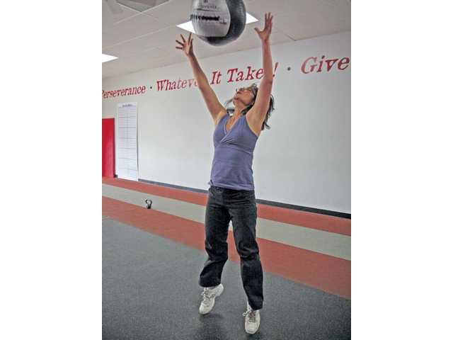 Holly Song of Stevenson Ranch exercises with a medicine ball at Results Fitness in Newhall. She has been a member of the gym since it opened nine years ago.