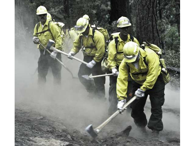 Sergeant Robert Davison, far left, fights fires while serving with the National Guard at the Butte County fire near Sacramento early July.