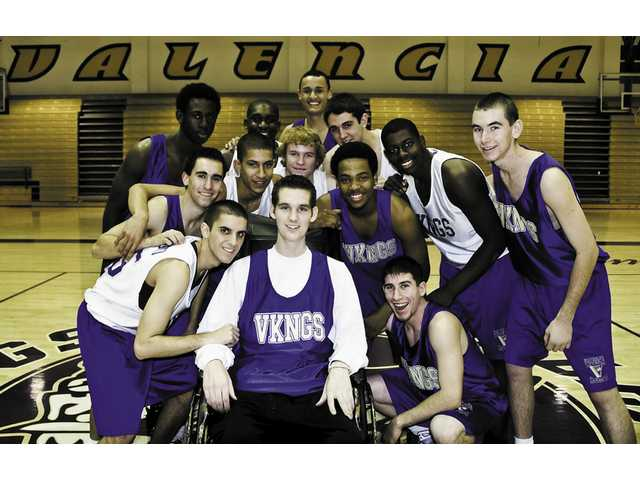 Valencia basketball players surround teammate David Stroud (center) at the Vikings gymnasium. Stroud, a senior who has battled two illnesses, plans to attend Vikings home games for the remainder of the season.