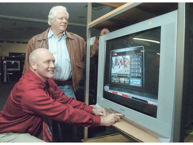 Rick Caston, of Caston's TV & Appliance, kneels to demonstrate the controls of a 36-inch, high-definition Sony TV that Rich Lipis, standing, won as the top prize of a holiday food drive held by The Signal.