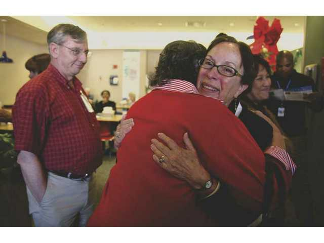 Daniele Washburn, an employee at Henry Mayo Newhall Memorial Hospital, is greeted by co-workers in the hospital's cafeteria where her retirement party took place Tuesday afternoon. Washburn has been involved with Newhall Memorial for 40 years.