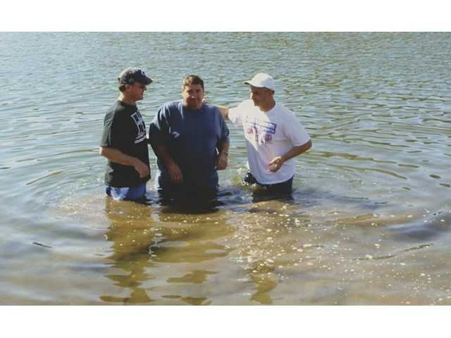 Oak Hill Bible Church's Pastor Jeff Noe, left, and executive director, Mark Giganti, right, baptize member Rick Taylor.
