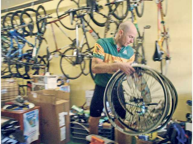Roger Hasper, owner of Newhall Bicycle Company, moves inventory into the store's new location on Main St. in Newhall on Saturday.
