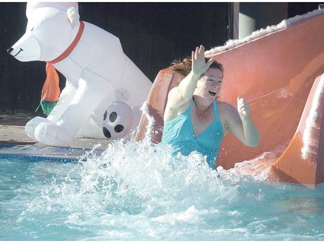 Mary Tesselar, of Saugus, slides into the 48 degree water at the Santa Clarita Sports Complex Aquatic Center pool as part of the Glacier Slide Polar Bear Swim on New Year's morning.  An inflated polar bear decorated the pool for the event.
