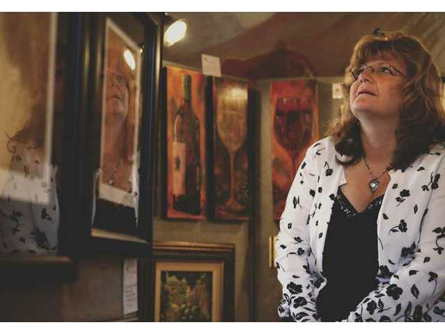 Sandy Fisher, from Saugus, admires artwork on display from fellow members of the Santa Clarita Artists' Association at the Tesoro Adobe Historic Park Saturday morning. The display, which goes on all year, will rotate different works from local artists.