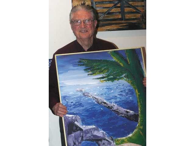 Canyon Country resident Joe Hendricks holds one of his ocean scene paintings.