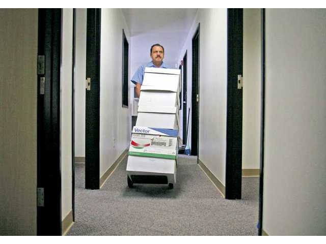 College of the Canyons custodian Carlos Melgoza help move boxes into the new offices for the campus' Academic Affairs and Payroll departments on Monday.