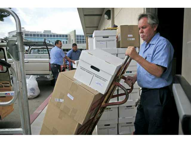 College of the Canyons custodian Juan Diaz, right, and others help move boxes into the new offices for the campus' Academic Affairs and Payroll departments on Monday afternoon.