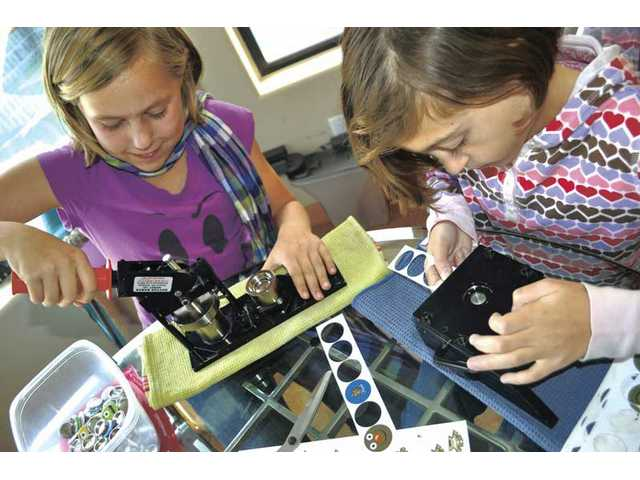 Pico Canyon Elementary School fifth-graders Caitlin Buckley, left, and Riley Villiers-Furze make buttons with a button-making machine for their new business, Buckville Buttons.