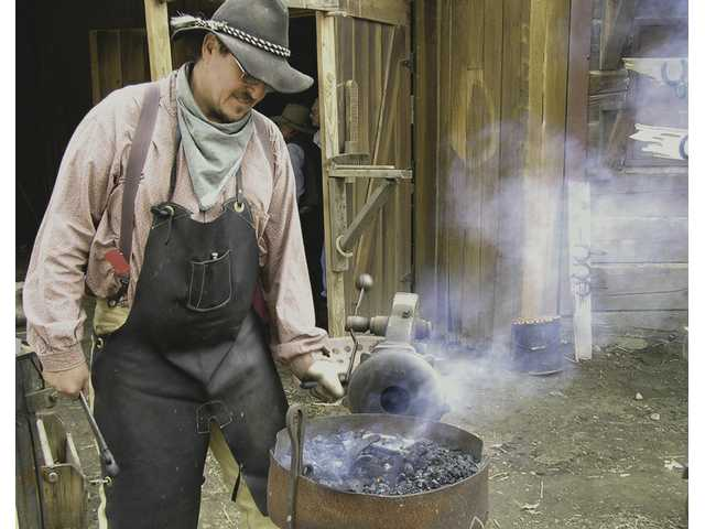 The Melody Ranch blacksmith fires up a horseshoe at his shop on Main Street during the 2008 Santa Clarita Cowboy Festival.