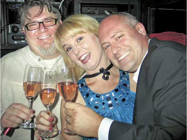 Left to right, Peter Goossens celebrates New Year's Eve with April and Jason Price with a toast.