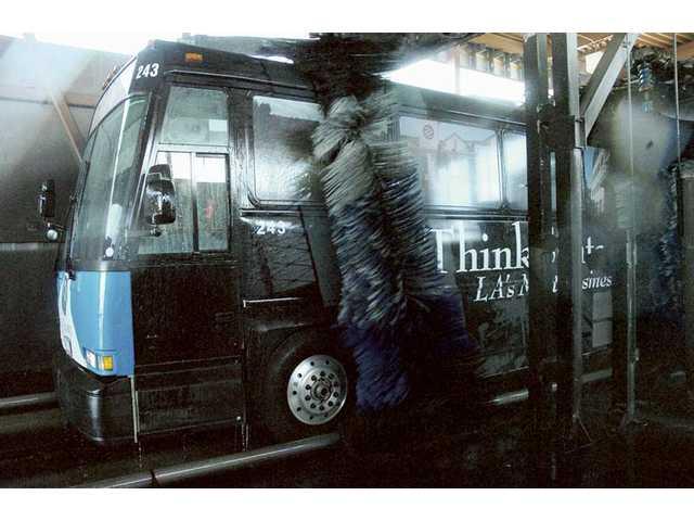 A Santa Clarita transit bus with the new ThinkSantaClarita.com paint scheme goes through the automated bus wash at the City of Santa Clarita Transit Maintenance Facility on Wednesday.