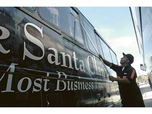 A Santa Clarita transit bus with the new Think Santa Clarita paint scheme is dried by utility worker Ronald Joma after going through the automated bus wash at the City of Santa Clarita Transit Maintenance Facility in Santa Clarita on Wednesday.