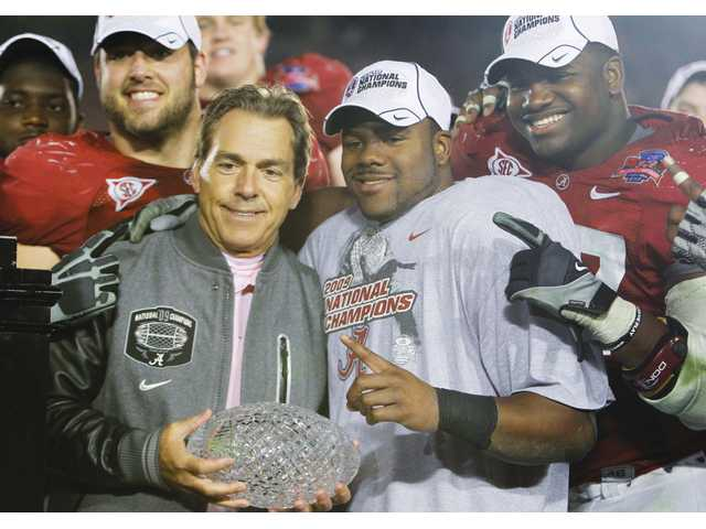 Alabama head coach Nick Saban holds up the championship trophy with Heisman Trophy-winning running back  Mark Ingram, right, after beating Texas 37-21 in the BCS National Championship game Thursday at the Rose Bowl in Pasadena.
