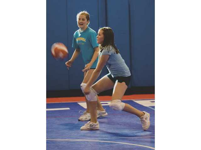 Elite Volleyball Camp Coach Erika Lilley demonstrates to 12-year-old Alexis Gotham the correct way to move the arms before jumping to the net and hitting the ball.