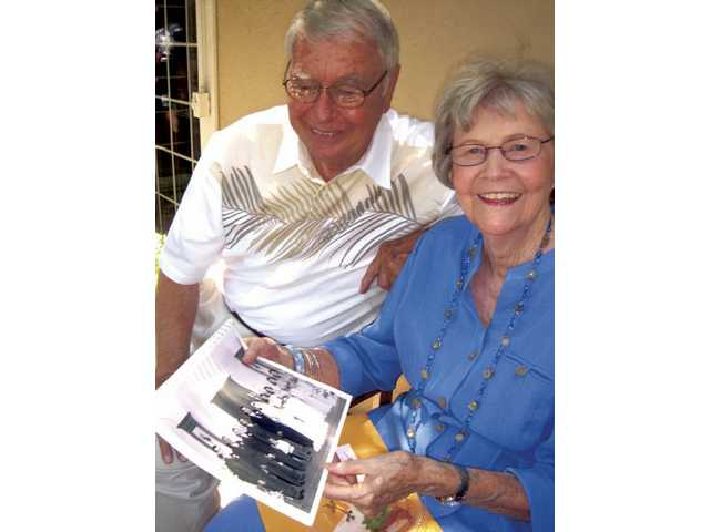 Lester and Millie Tanner look through their wedding photos.