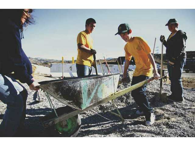 Ricky Hoefert, 12, of Boy Scout Troop 2's Falcon Patrol, pushes a wheelbarrow full of gravel as fellow scouts look on Saturday at the Santa Clarita Valley Winter Emergency Shelter. The boys were among volunteers who helped set up more parking spaces and performed maintenance on the shelter.