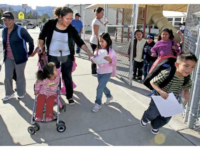 Sandra Diaz and 2-year-old daughter Kelly Gutierrez, in stroller, pick up first-grader Daisy Besa from Newhall Elementary School on Monday after school is dismissed.